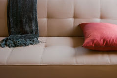 Sofa with Throw Blanket. White leather couch or sofa with gray throw blanket and pink pillow Stock Photo