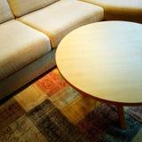 Sofa und Couchtisch auf einem bunten Teppich Lizenzfreie Stockfotos