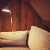 Sofa und Lampe in einem Raum mit hölzernen Wänden Stockfoto