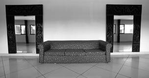 Sofaen och avspeglar i korridor royaltyfria foton