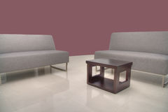 Sofas with coffee table with Maroon Wall Royalty Free Stock Photos