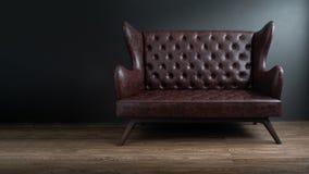 Soffa av det svarta läderanseendet i mitt på konkret golv mot den mörka gråa väggen med kopieringsutrymme Soffa för tappningbrunt arkivbild