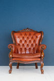 Soffa för läder för brunt för klassiker för fåtölj för brunt för tappningläderlyx och gammal blå bakgrund Royaltyfria Bilder