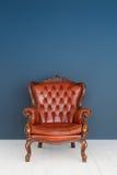 Soffa för läder för brunt för klassiker för fåtölj för brunt för tappningläderlyx och gammal blå bakgrund Royaltyfria Foton