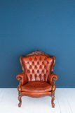 Soffa för läder för brunt för klassiker för fåtölj för brunt för tappningläderlyx och gammal blå bakgrund Arkivbilder