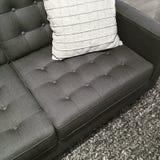 Soffa, filt och kudde i skuggorna av grå färger arkivbild