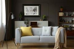 Soffa med grå färger och gula kuddar, lampa, målning och cupb royaltyfri foto