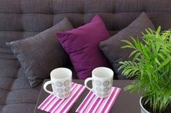 Soffa med kuddar och två koppar på en tabell royaltyfria foton