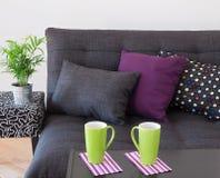 Soffa med ljusa kuddar och gräsplankoppar på en tabell Arkivfoto