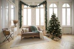 Soffa och julgran nära fönster arkivfoton