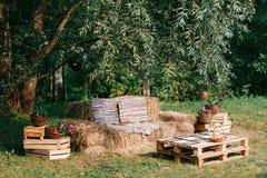 soffa som göras från sugrör, utomhus- möblemang, cowboyparti trä av en palett Arkivfoton