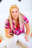 soffa spännande sittande hållande ögonen på kvinna för tv Royaltyfria Bilder