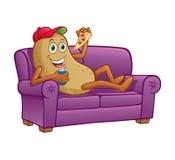 Soffapotatis som äter pizza på soffan arkivbilder