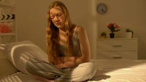 Sofferenza dal letto domestico di seduta di mal di stomaco, sanità, malattia dell'adolescente video d archivio