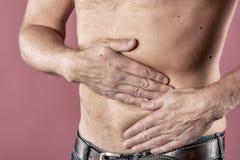 Sofferenza dell'uomo dal dolore nel suo lato Fondo rosa Mal di stomaco, pancreas, reni fotografia stock libera da diritti