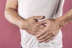 Sofferenza dell'uomo dal dolore nel suo lato Fondo rosa Mal di stomaco, pancreas, reni immagine stock