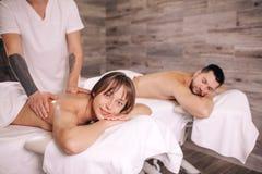 Sofferenza della donna e del giovane dalla scoliosi che ottiene massaggio immagine stock