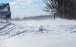Soffiando, neve di spostamento attraverso una strada campestre Immagini Stock