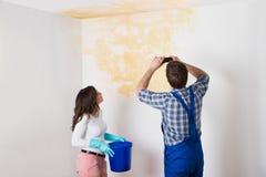 Soffitto di With Woman Photographing del tuttofare a casa Fotografia Stock Libera da Diritti