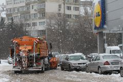 Sofia, Bulgaria – Feb 26, 2018: A snowplow machine cleans parking lot of LIDL store from snow after big snowstorm. Sofia, Bulgaria – Feb 26, 2018: A Royalty Free Stock Photo