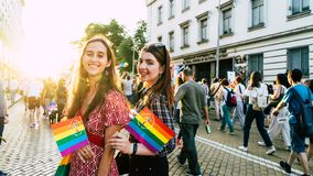 Sofia / Bulgaria - 10 June 2019: smiling Girls in LGBT parade with rainbow flag in the street. Gay and lesbian festival supporting