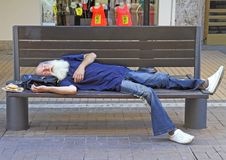 Old man is sleeping on a bench outdoor in Sofia, Bulgaria Stock Photos