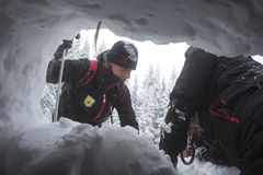 Red Cross rescuers through snow hole. Sofia, Bulgaria - January 18, 2017: Rescuers from Mountain rescue service at Red Cross organization participate in a Royalty Free Stock Photography