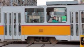 SOFIA, BULGARIA - SEPTEMBER 2016: Two tram cross the street. Two old trams cross the street stock footage