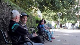SOFIA, BULGARIA - SEPTEMBER 2016: Two old men talk sitting on bench in park stock footage