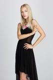 Sofistikerad dam i den svarta silkeslena aftonklänningen som poserar behagfullt Royaltyfri Bild