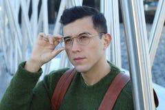 Sofistikerad ung etnisk man som justerar hans glasögon arkivfoto