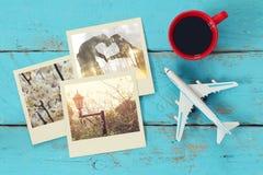Sofortige Fotografien der Reise nahe bei Tasse Kaffee und Flugzeug Stockfoto