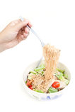 Sofortige Nudeln rühren sich mit Gemüse, Schweinefleisch, Wurst auf Gabel in der Hand Lizenzfreie Stockfotografie