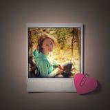 Sofortiges Foto des schönen Mädchens und kleines rotes Papierherz Lizenzfreies Stockbild