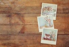 Sofortiges polaroidfotoalbum auf hölzernem Hintergrund Lizenzfreie Stockfotografie