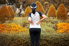 Sofrimento desportivo da mulher da dor em ferimento da cintura após movimentar-se de corrida do exercício do esporte e no exercíc foto de stock