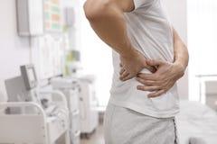 Sofrimento do homem da dor do flanco no escritório do ortopedista fotos de stock
