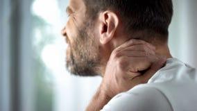 Sofrimento masculino da dor de pescoço na manhã, colchão incômodo, cuidados médicos imagens de stock