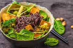 Sofrito asiático del vegano con el queso de soja, los tallarines de arroz y las verduras, fondo oscuro fotos de archivo libres de regalías