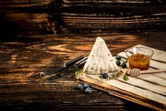Soft Adyghe cheese with fresh berries, honey on rustic background. space for text royalty free stock image