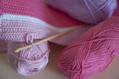 Soft, baby pink yarn for crocheting or knitting. Horizontal shot of detailed baby blanket and yarn balls in delicate pink hues and with wooden, bamboo hook Royalty Free Stock Photography