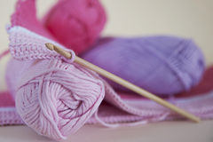 Soft, baby pink yarn for crocheting or knitting. Horizontal shot of detailed baby blanket and yarn balls in delicate pink hues and with wooden, bamboo hook stock photo