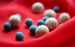 Soft beads. White and blue soft beads on the red fabric royalty free stock photos