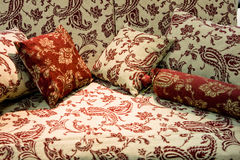 Soft beige sofa with red pillows. In bedroom Stock Image