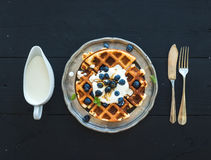 Soft Belgian waffles with blueberries, honey and. Whipped cream on vintage metal plate over black wooden background, top view Stock Images
