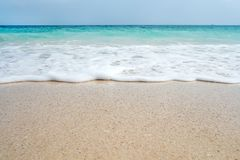 Soft blue ocean wave on sandy beach. Background. White sand on the beach with turquoise water. An exotic island in the Indian ocean Stock Photography