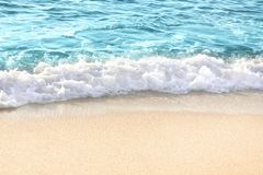 Soft blue ocean wave on sandy beach royalty free stock images