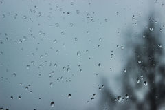 Soft and blur conception. Drops of water on the window in winter season. Background with drop of water closeup. Stock Photos