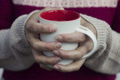 Soft and blur conception.A woman holds a hot cup of tea and warms his hands. Stock Images