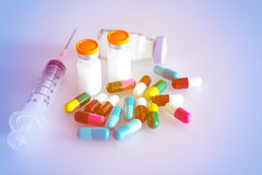 Soft and blurred Capsules pills and syringe. Royalty Free Stock Photos